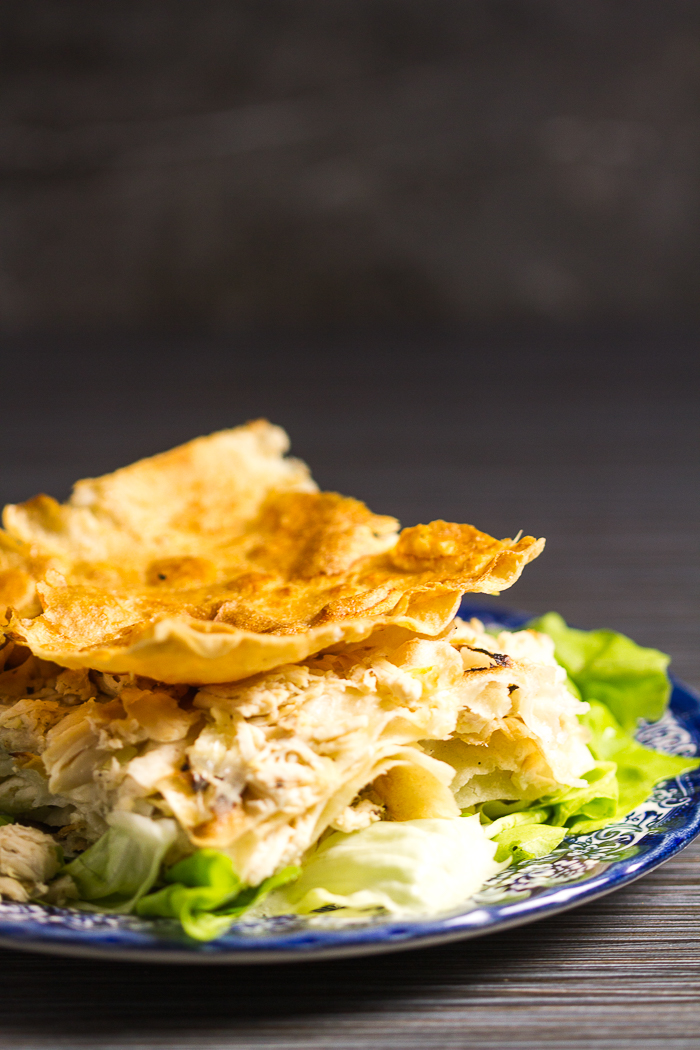 The most tender and soft chicken pie infused with homemade chicken broth. First the chicken is brought to boil until it gives its all to the broth, and then shredded. Shredded pieces are used in between crunchy phyllo (or tortillas even), infused with broth and baked.